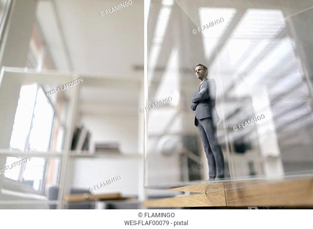 Businessman figurine standing in modern office, looking through glass pane