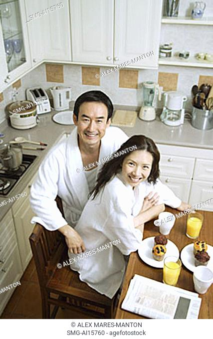 Couple sitting in kitchen, smiling at camera, high angle view