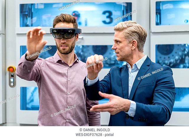 Two businessmen with AR glasses in a modern factory