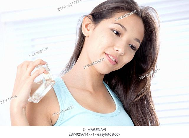 Young woman holding perfume bottle