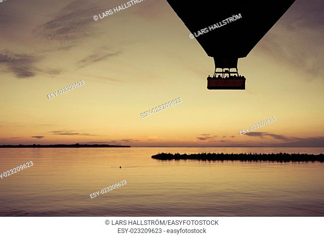 Beautiful nature scene with silhouette of hot air balloon flying over lake at sunset