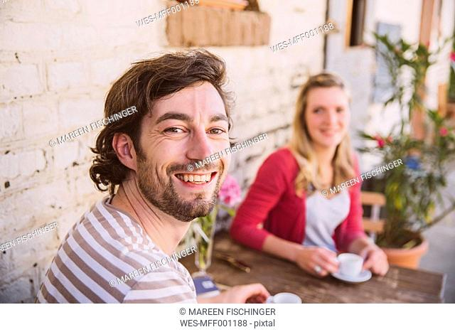 Germany, Northrhine Westphalia, Bornheim, Couple sitting in courtyard, drinking coffee