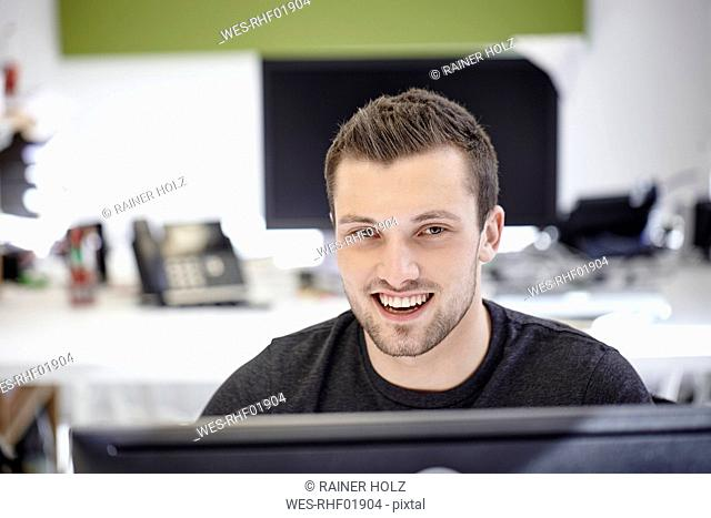 Young man working in office, looking at camera
