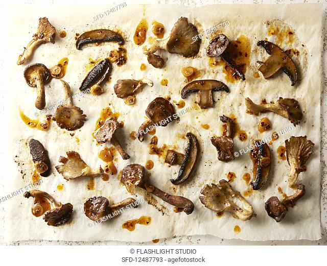 Roasted mixed mushrooms with garlic chili oil on parchemnt