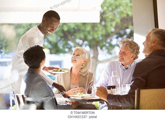 Waiter serving food to couples at restaurant table