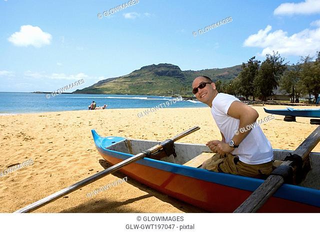 Side profile of a mid adult man sitting in a boat on the beach, Nawiliwili Beach Park, Kauai, Hawaii Islands, USA
