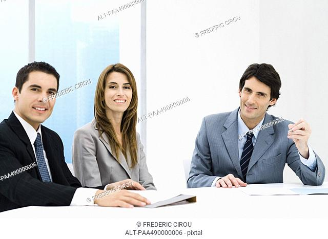 Business associates having meeting, all smiling at camera