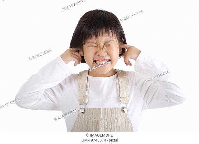 Girl holding fingers in ears, portrait
