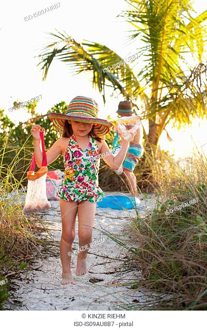 Girl and brother collecting seashells at beach, Sanibel, Florida, USA