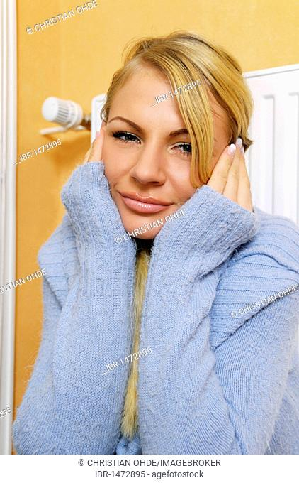 Young woman sitting in front of the heater, freezing
