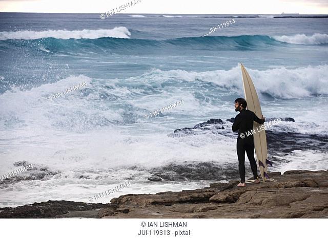 Surfer with surfboard standing on rocks wearing wetsuit watching ocean