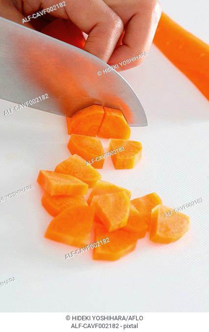 Close up of woman's hands slicing carrots with a kitchen knife