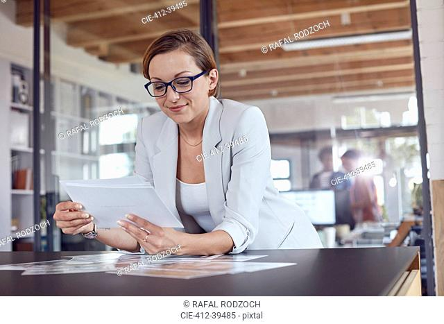 Female design professional reviewing photograph proofs in office