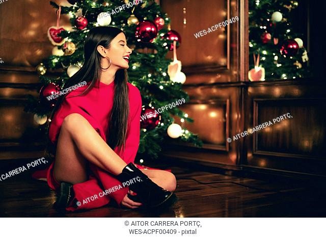 Laughing teenage girl sitting on the floor in front of Christmas tree