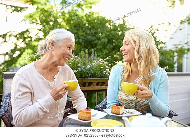 daughter with senior mother drinking tea at cafe