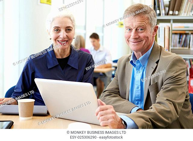 Two Mature Students Working Together In Library Using Laptop