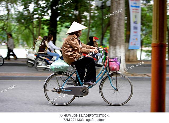 Woman cycling in Hanoi, North Vietnam