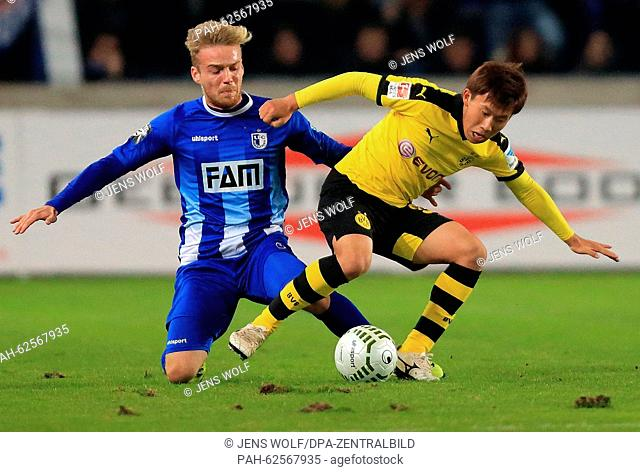 Magdeburg's Nils Butzen (L) and Dortmund's Mitsuru Maruoka vie for the ball during the soccer friendly between 1. FC Magdeburg and Borussia Dortmund at the...