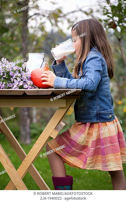 Girl drinking a glass of milk outdoor in the garden. Slovenian countryside