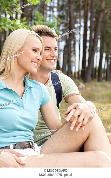 Thoughtful hiking couple looking away while relaxing in forest