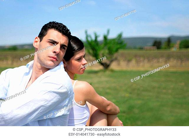 couple sitting back to back in a field