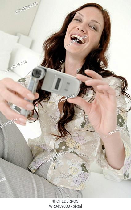 Portrait of a mid adult woman taking a picture with a mobile phone and laughing