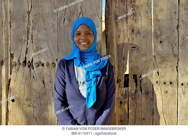 Young woman with headdress, against a wooden door, portrait, Karima, Northern, Nubia, Sudan