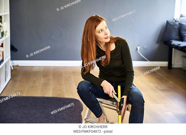 Redheaded woman with hammer and water level sitting on step ladder