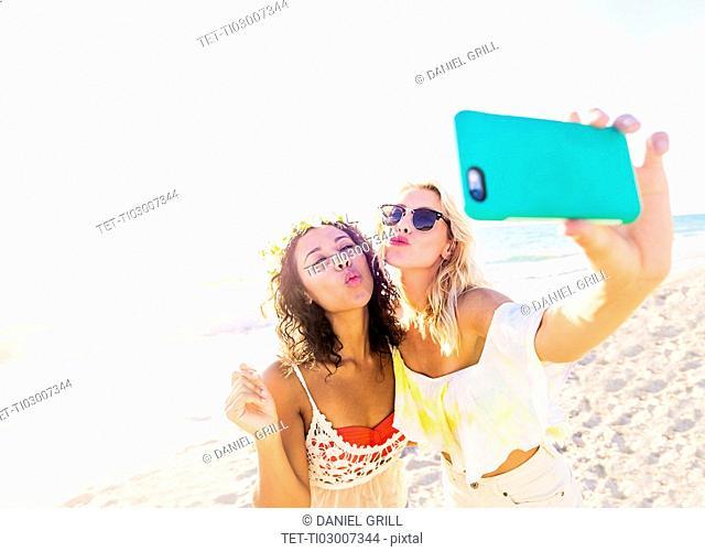 Female friends taking selfie on beach