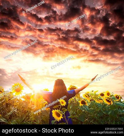 Woman with raised hands looks on the sundown. Harmony and unity with nature