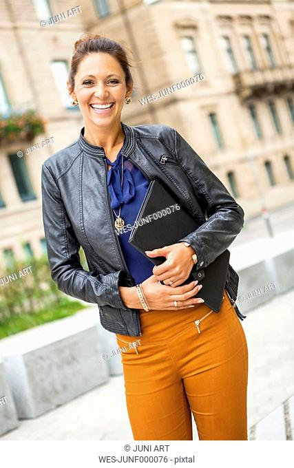 Portrait of happy young woman wearing leather jacket holding a folder