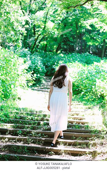 Young Japanese woman surrounded by green in a city park