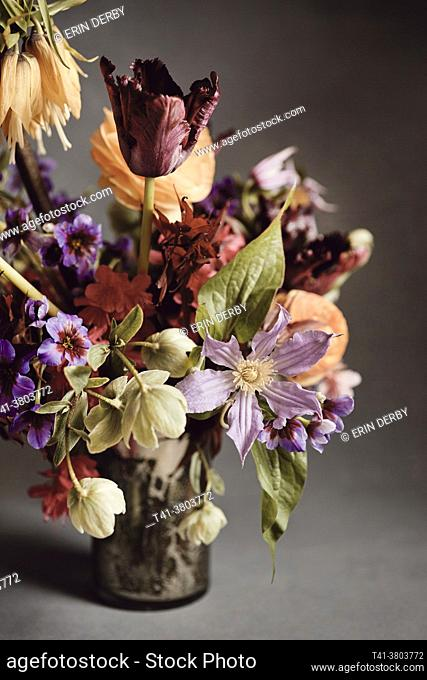 A bouquet of red, orange, purple, green and blue flowers in a mercury glass vase against a grey backdrop