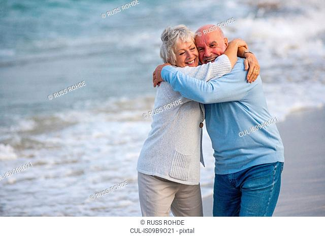 Couple hugging and laughing by seaside