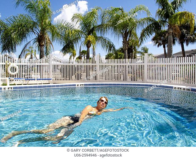 A woman swimming in a swimming pool in a tropical location