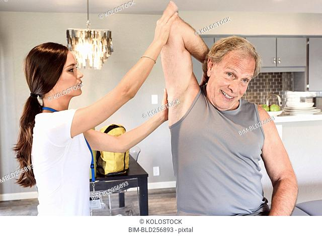 Physical therapist helping man stretch arm