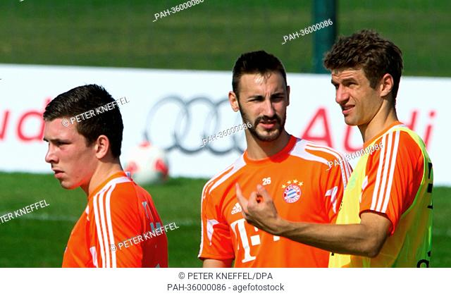 Pierre Emile Hojbjerg (L-R), Diego Contento uand Thomas Mueller of Bundesliga soccer club Bayern Munich are pictured during a training session in Doha, Qatar