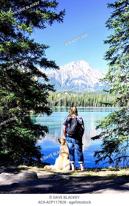 A woman and her Golden Retriever pause while hiking around Lac Beauvert in Jasper National Park in Jasper, Alberta, Pyramid Mountain is in the background