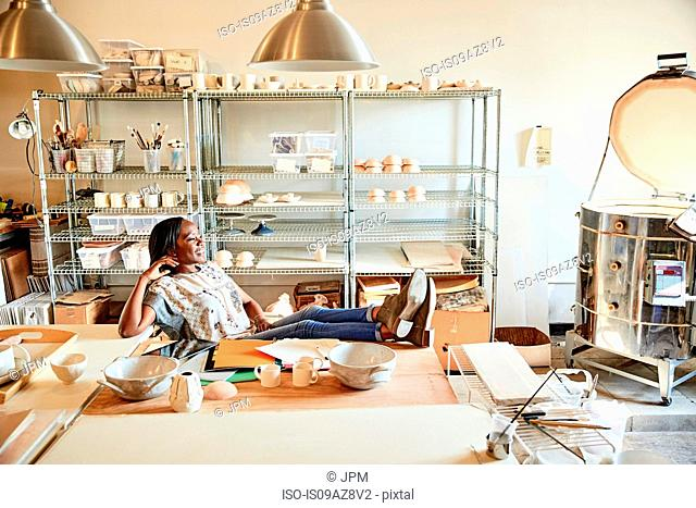 Woman in pottery workshop feet up looking away