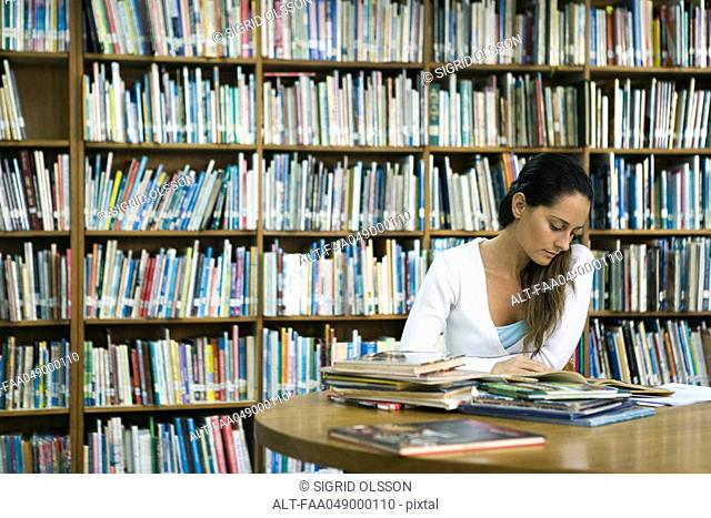 Woman reading book at table in library