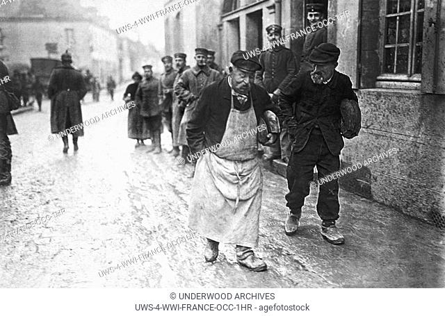 France: c. 1916.Two elderly French men leave with their loaves of bread that they had to request from the occupying German forces