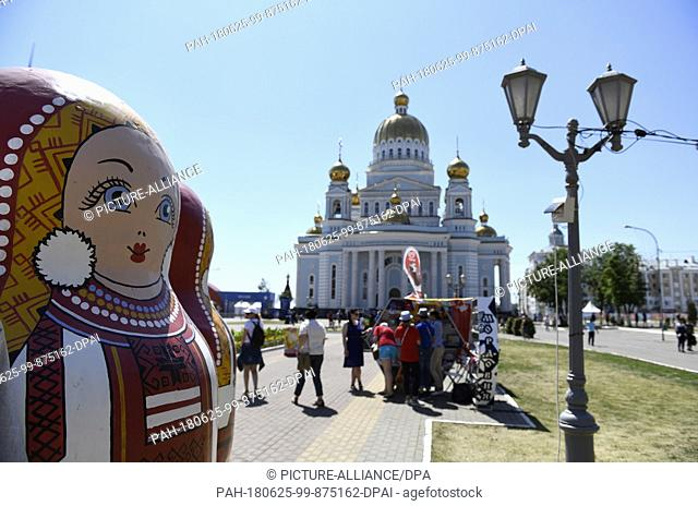 25 June 2018, Russia, Saransk: Soccer, World Cup: An oversized matryoshka doll before the Russian Orthodox Cathedral of St. Theodore Ushakov