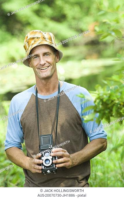 Portrait of a mature man holding a camera and smiling