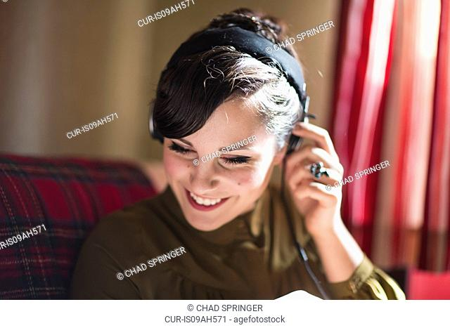 Young woman sitting on sofa, listening to music on headphones
