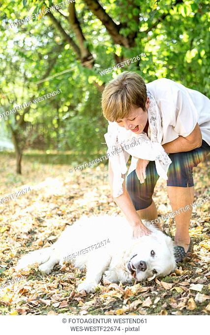 Senior woman petting dog outdoors