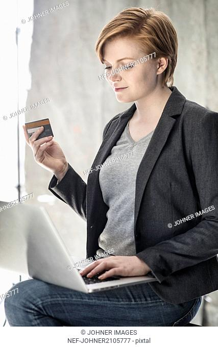 Woman with bank card using laptop
