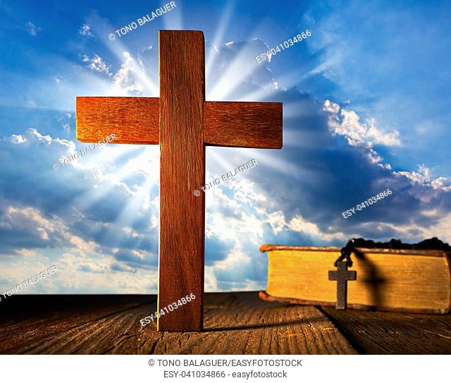 Christian wood cross on blue sky wooden made with Bible and rosary beads