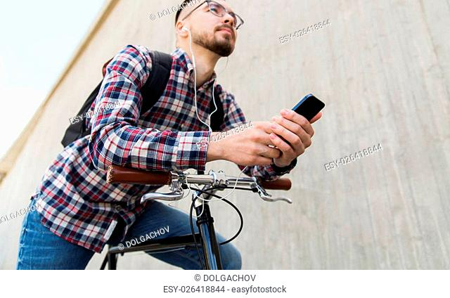 people, travel, technology, leisure and lifestyle - close up of young hipster man in earphones with smartphone and fixed gear bike listening to music on city...