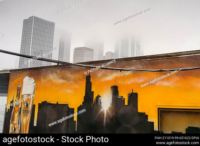 19 October 2021, Hessen, Frankfurt/Main: Frankfurt's skyscrapers disappear in the haze of grey rainy weather, while below is a depiction of the cityscape at...