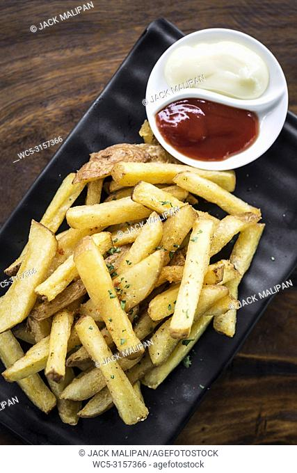 french fries chips side snack with diping sauces on wooden table